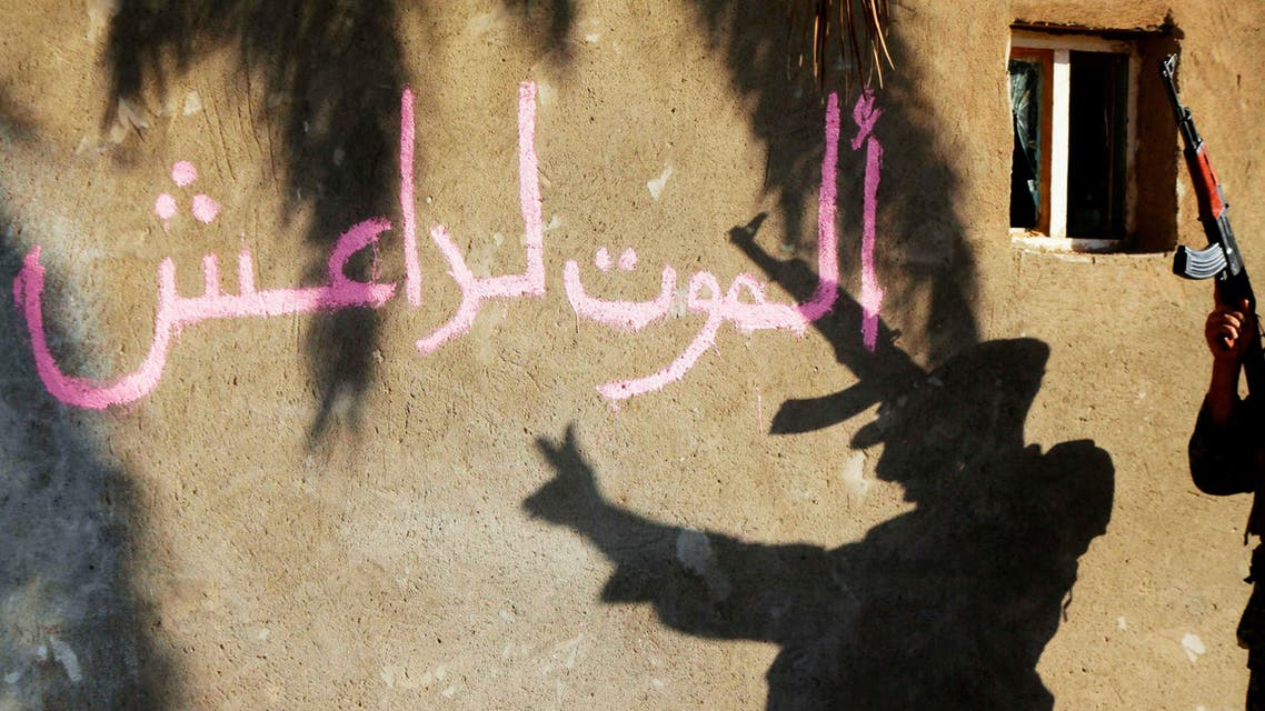 The shadow of a Shi'ite fighter flashing the 'V' sign while celebrating after taking control of Jurf al-Sakhar from Islamist State militants, is cast on a wall October 26, 2014. reuters
