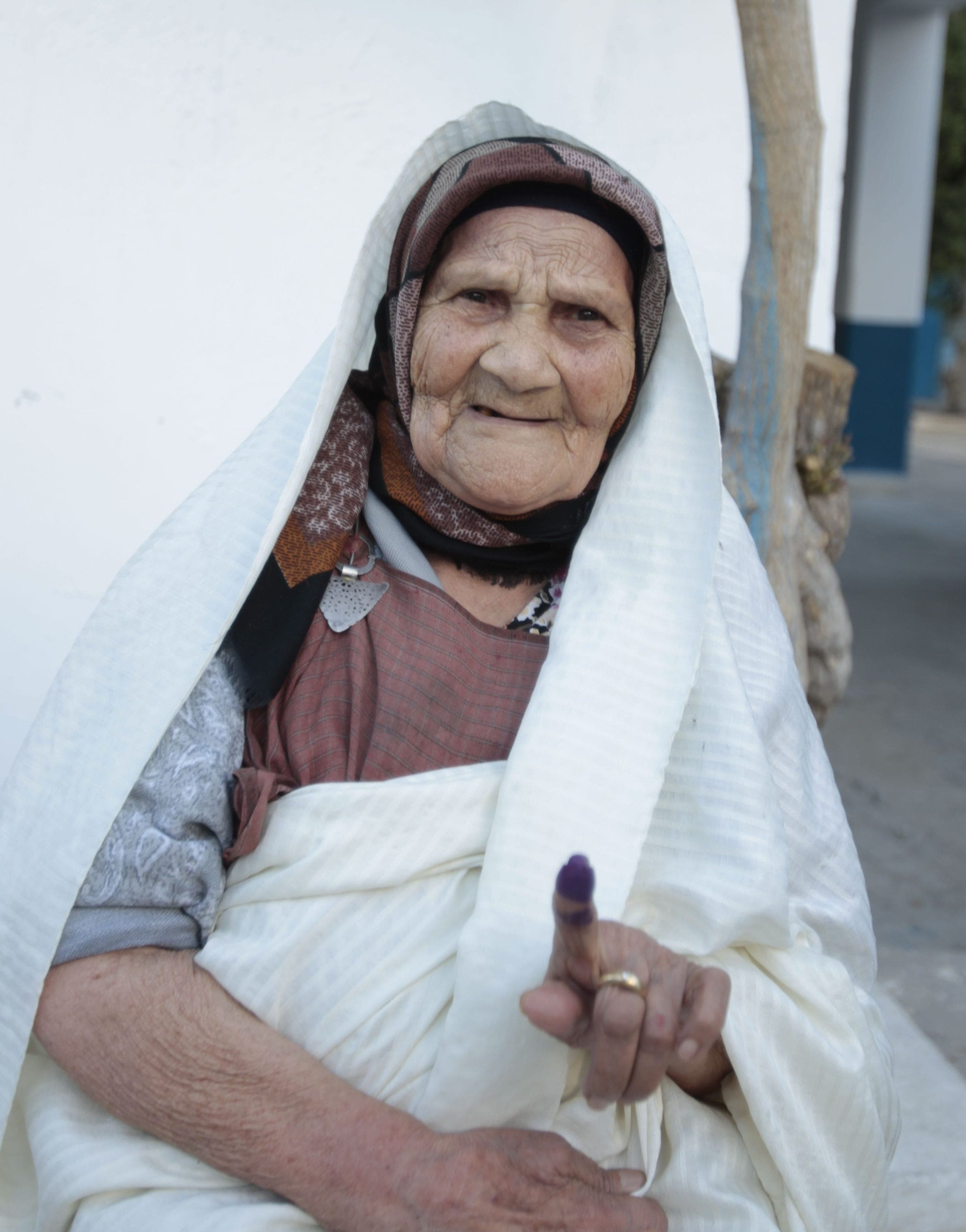 A voter raises her ink-stained finger after casting her vote at a polling station in Tunis October 26, 2014.