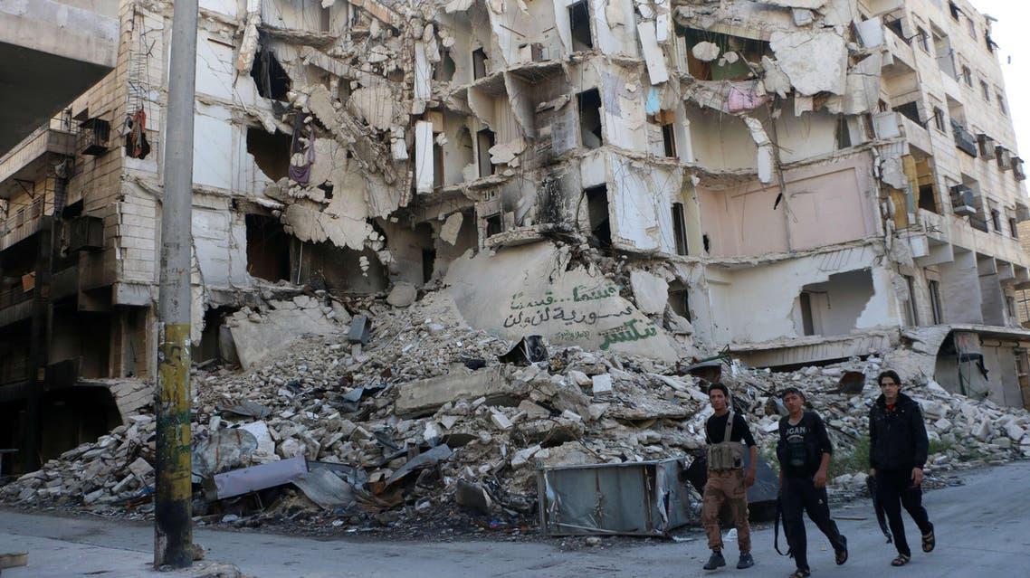Rebel fighters walk past a heavily damaged building on October 23, 2014. (File photo: AFP)