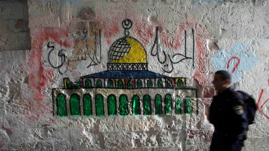 An Israeli police officer walks past a mural of the Dome of the Rock near the entrance to the compound known to Muslims as Noble Sanctuary and to Jews as Temple Mount, in Jerusalem's Old City