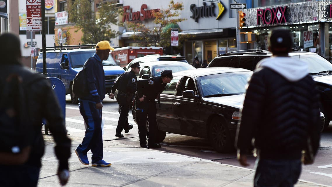 Two New York Police Department (NYPD) officers talk to the driver in a car near Jamaica Avenue and 162nd street in Queens on Oct. 24, 2104 (AFP)