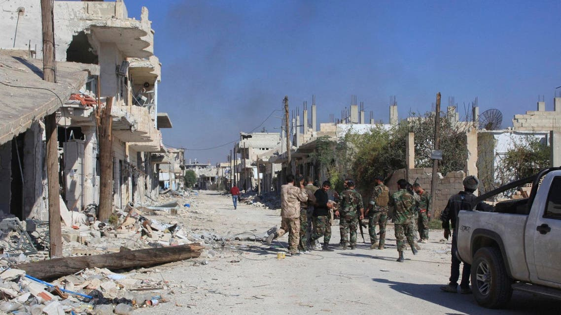 Smoke rises as forces loyal to Syria's President Bashar al-Assad gather along a damaged street in the town of Morek after regaining control of the area October 24, 2014. (Reuters)
