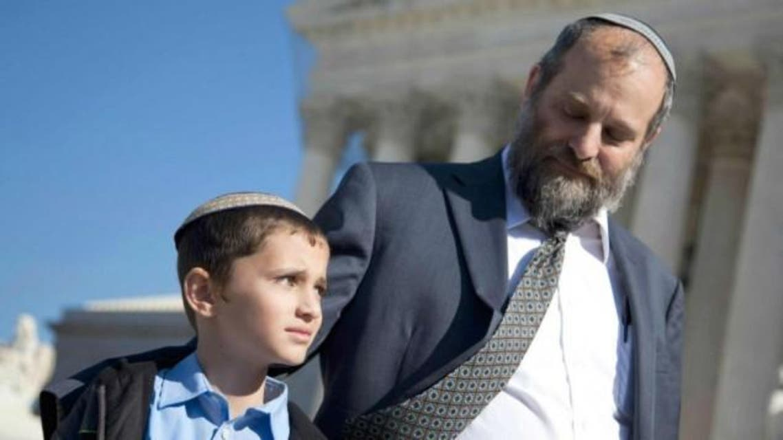 Ari Zivotofsky (right), stands with his nine-year-old son, Menachem, outside the Supreme Court in Washington, DC, November 7, 2011. (Photo courtesy: AP)
