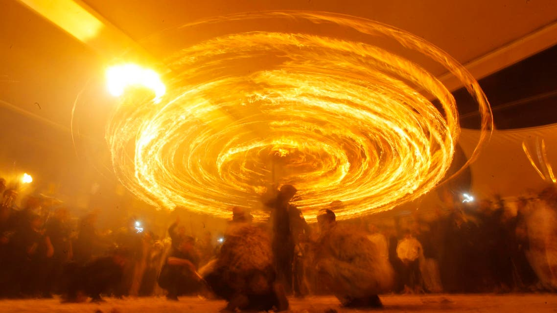 Shiite Muslims perform with fire during commemorations for Ashoura in Najaf, November 3, 2014. (Reuters)