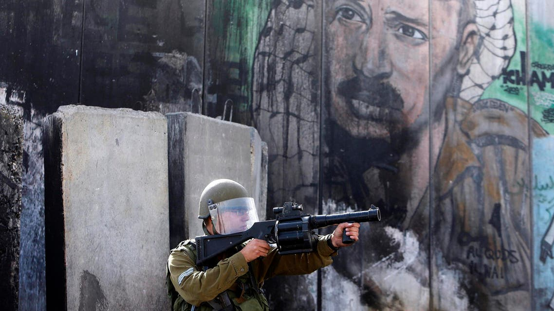 An Israeli soldier points his weapon toward Palestinian protesters during clashes following an anti-Israel demonstration at Qalandia checkpoint near the West Bank city of Ramallah Nov. 2, 2014. (Reuters)