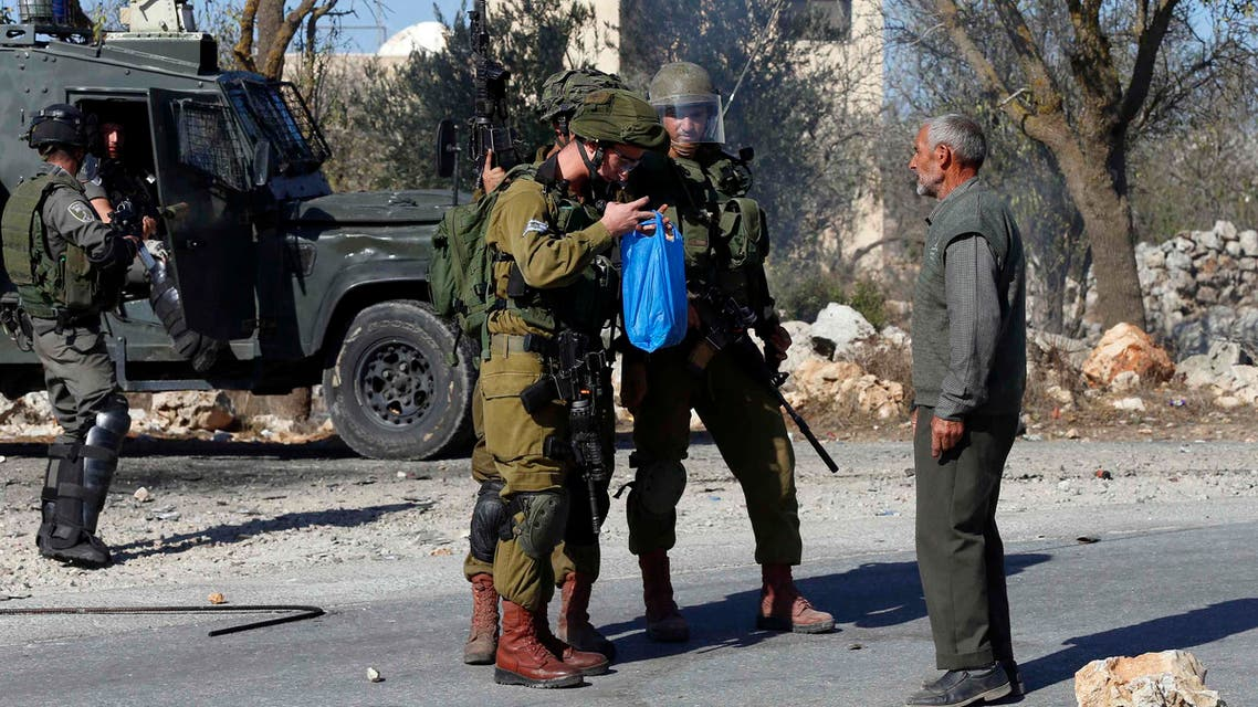 Israeli soldiers stop a Palestinian man as they check a bag he was carrying,. (Reuters)