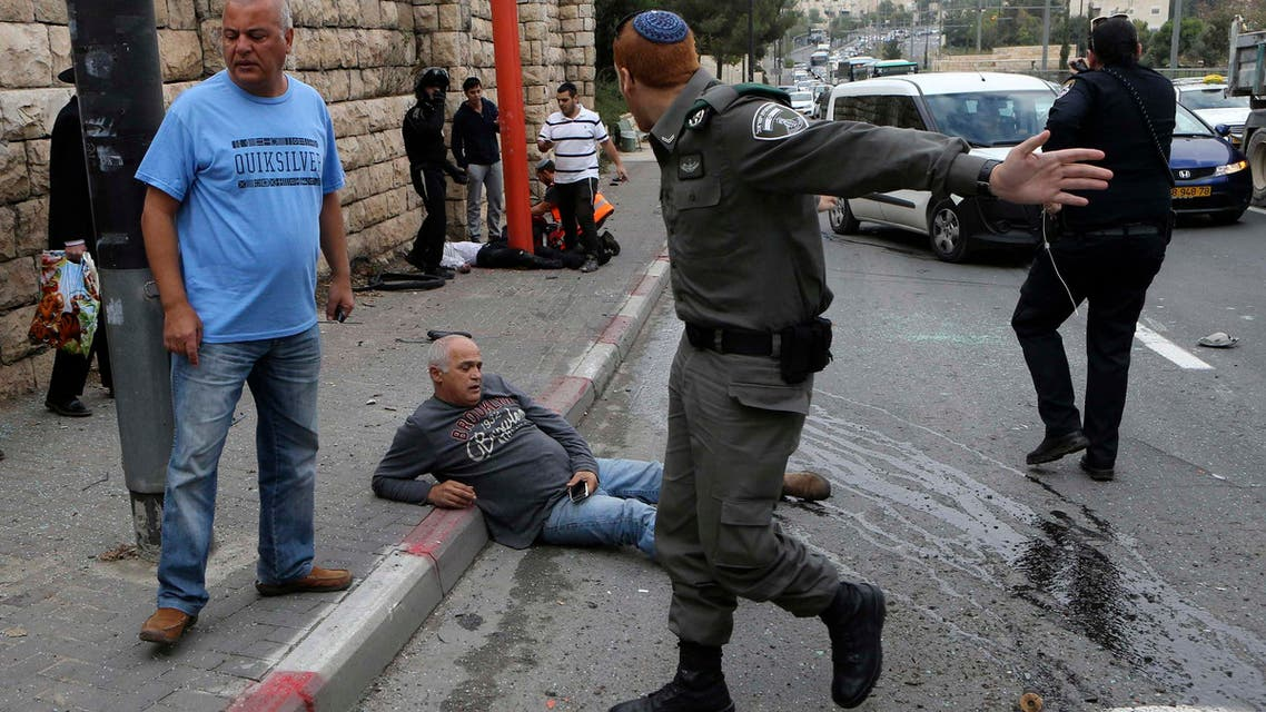 An Israeli border police officer gestures as a wounded man sits on the street after an attack by a Palestinian motorist in Jerusalem November 5, 2014. (Reuters)