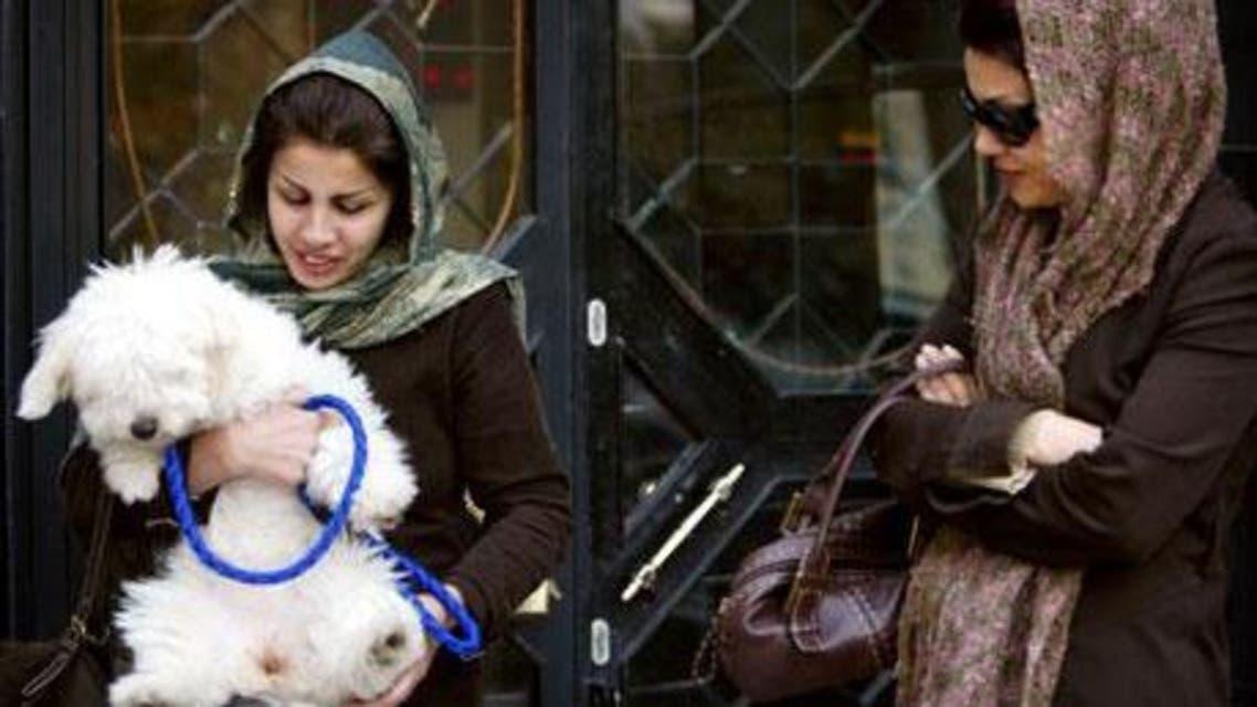 Iranian woman holds dod (Reuters)