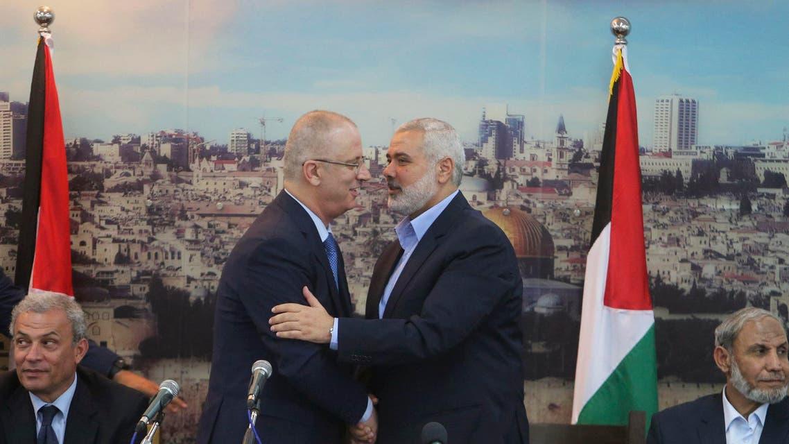 Senior Hamas leader Ismail Haniyeh (R) shakes hands with Palestinian Prime Minister Rami Hamdallah at Haniyeh's house in Gaza City Oct. 9, 2014.  (Reuters)