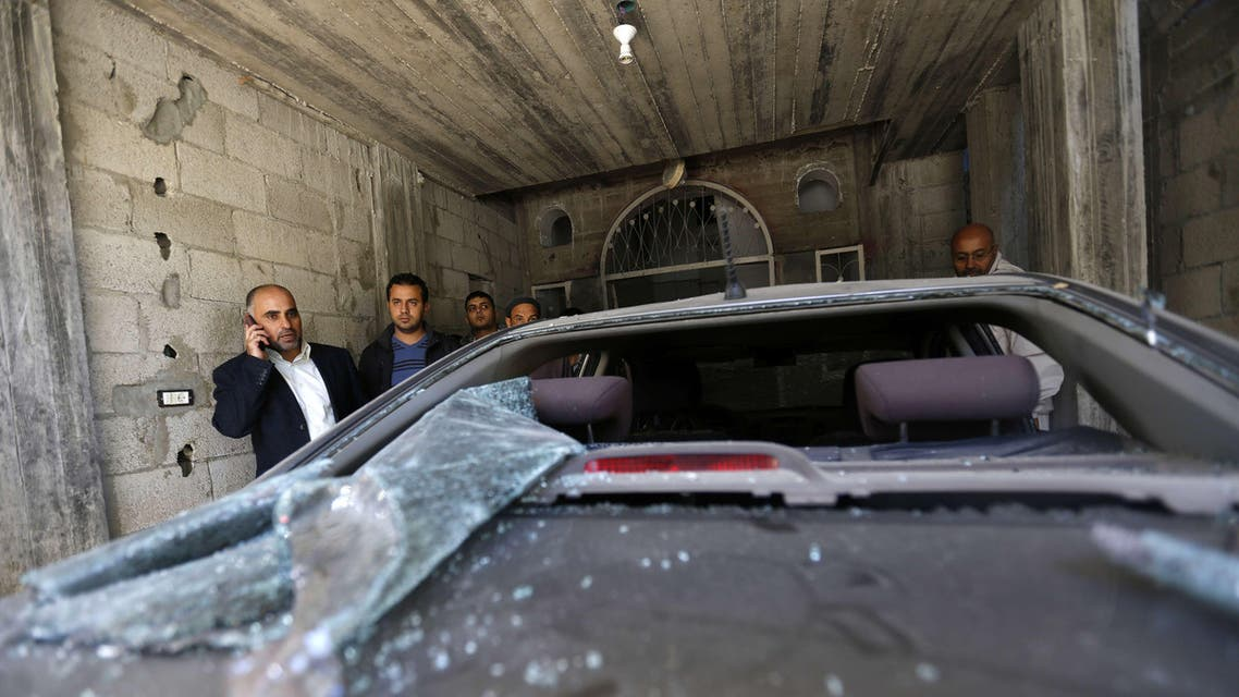 Fayez Abu Eitta (L), a Fatah leader in Gaza, speaks on the phone as he inspects the damage to his car in the parking lot of his home in Beit Lahya, northern Gaza Strip on Nov. 7, 2014. (AFP)
