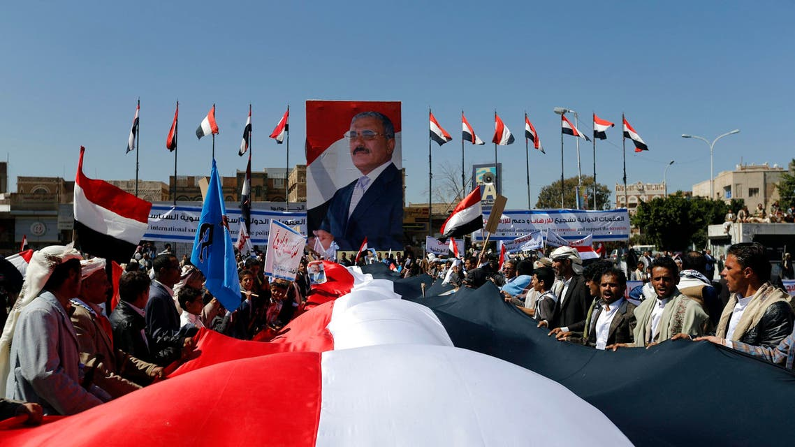 Supporters of Yemen's former President Ali Abdullah Saleh hold a huge Yemeni flag next to a poster of Saleh as they rally in his support in Sanaa November 7, 2014.