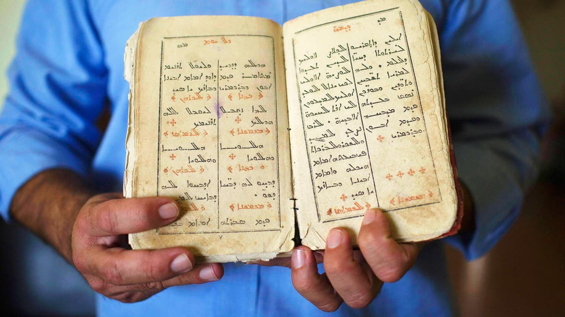 An Aramaic speaker, part of a group of a few hundred at most, holds a book of Aramaic hymns in the northern Israeli village of Jish October 25, 2014. reuters