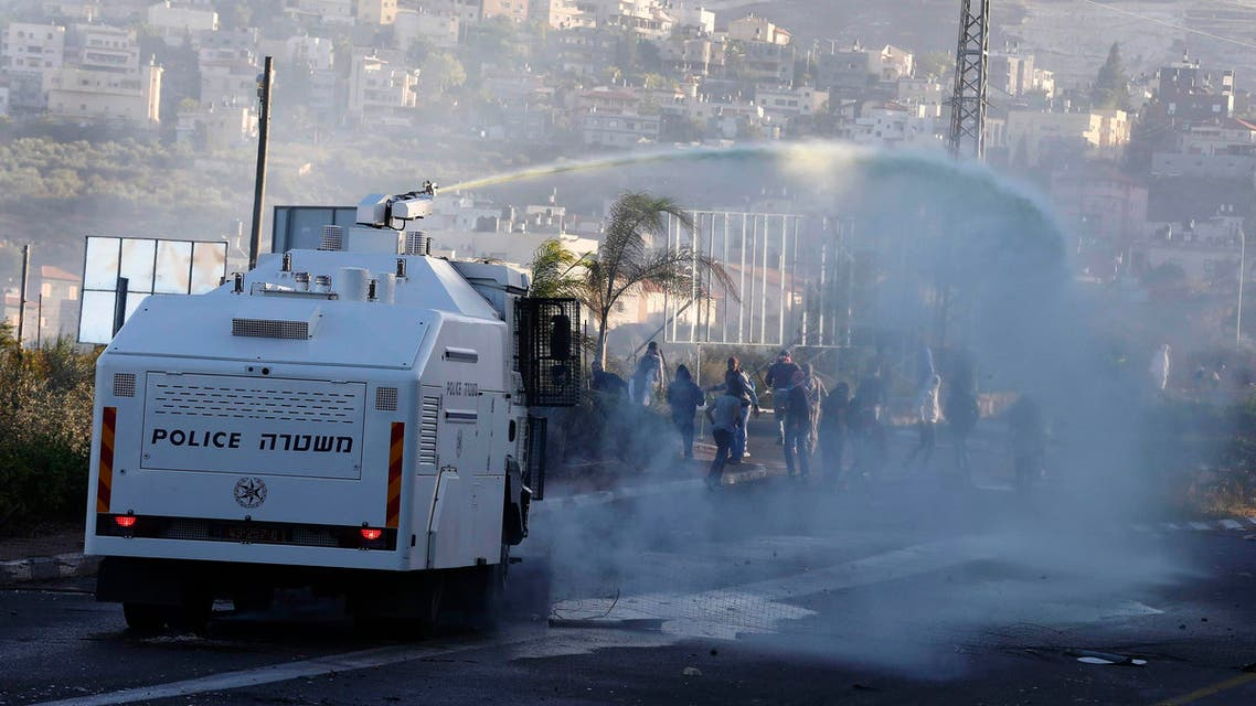 An Israeli police truck sprays water during during clashes between Arab youths and Israeli police at the entrance to the town of Kfar Kanna, in northern Israel, November 8, 2014. (Reuters)