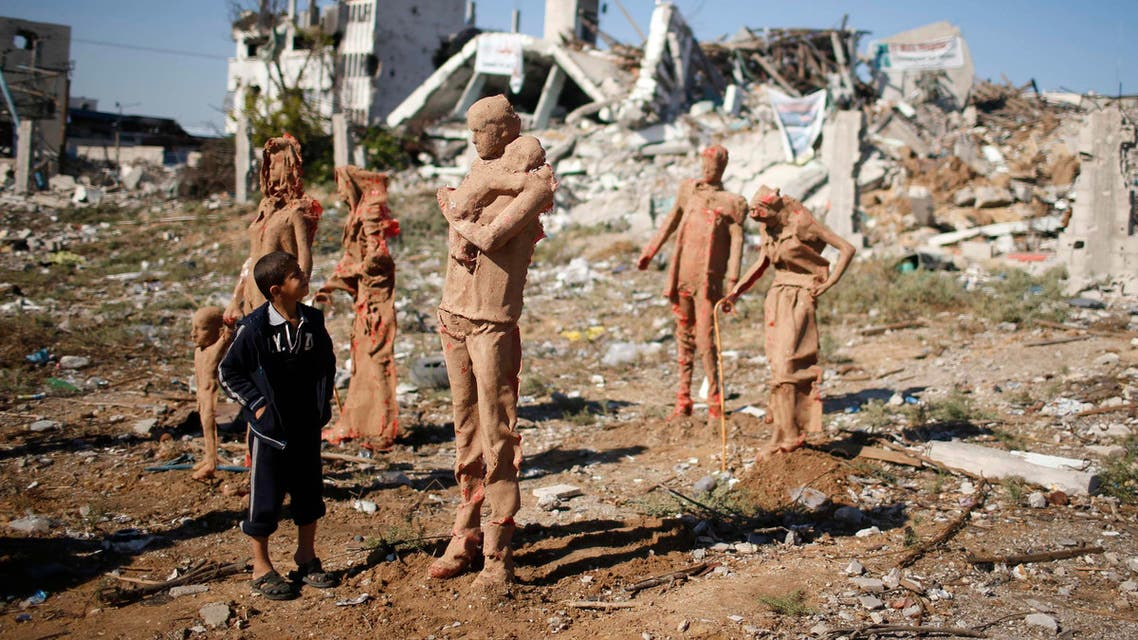 Palestinian boys look at statues that are made of fiberglass and covered with clay by Palestinian artist Eyad Sabbah, which are depictions for the Palestinians who fled their houses from Israeli shelling during the most recent conflict between Israel and Hamas, in the east of Gaza City. (Reuters)