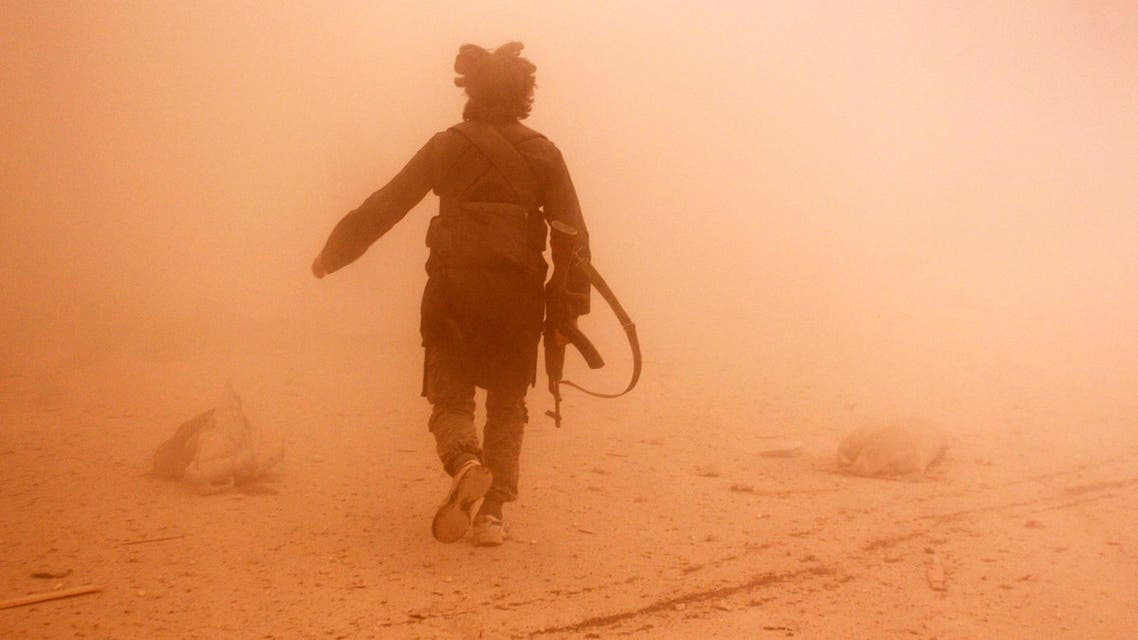 A rebel fighter runs through dust towards an area damaged by what activists said were barrel bombs dropped by warplanes loyal to Syria's President Bashar al-Assad, in Aleppo's al-Shaar neighborhood November 6, 2014 reuters