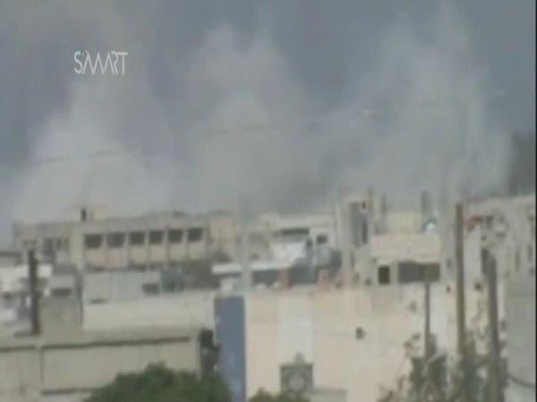 الدخان المتصاعد من جراء سقوط برميل متفجر على أحياء الرستن