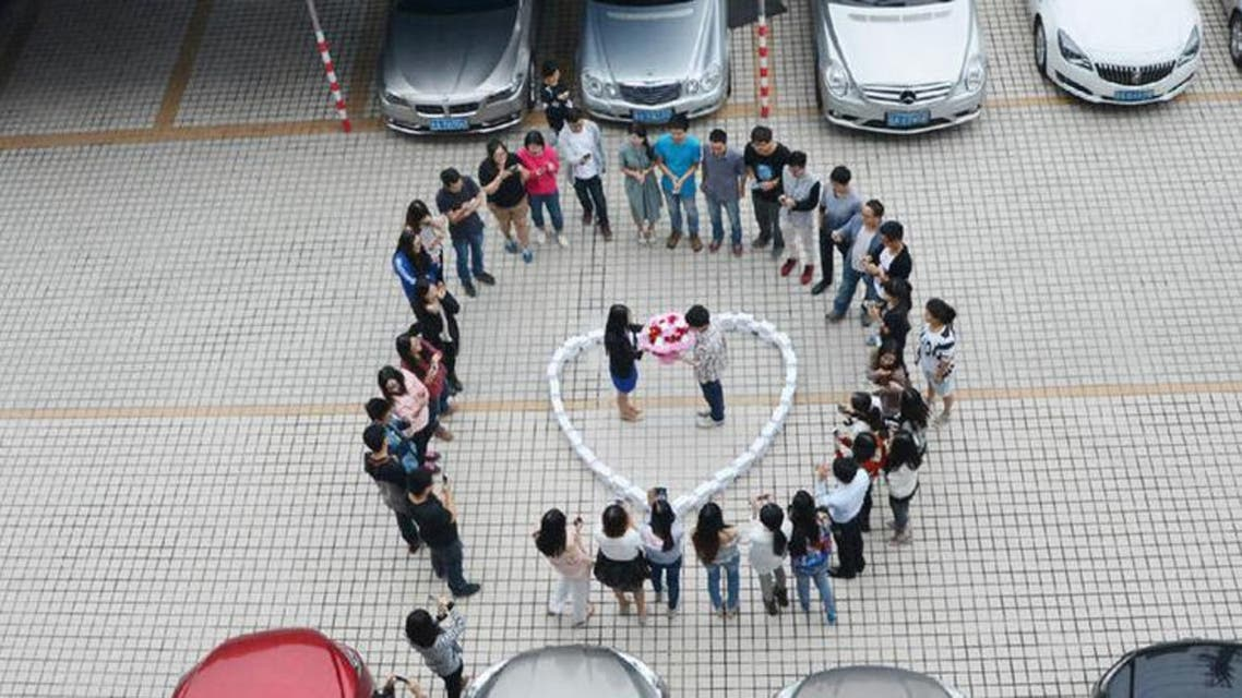 The young man standing with his girlfriend in a heart made out of 99 iPhone 6s. (Photo courtesy: xinhuanet.com)
