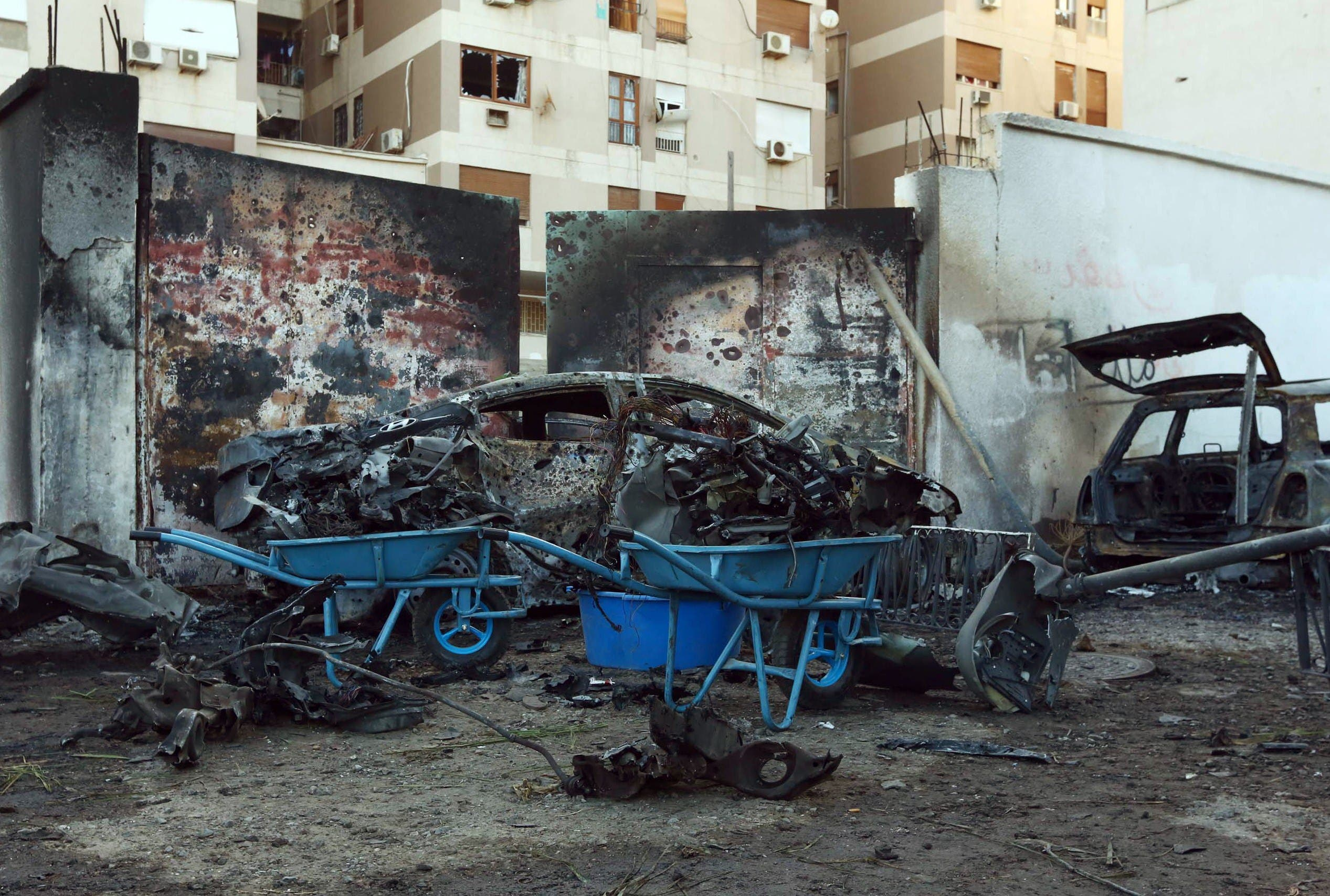 A destroyed vehicle is seen near the compound of the Egyptian embassy in the Libyan capital Tripoli on November 13, 2014 after it was targeted by a car bomb explosion. AFP