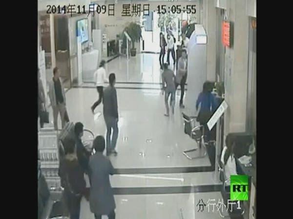 """فيديو.. لص """"غبي"""" يسرق أموال امرأة داخل بنك"""