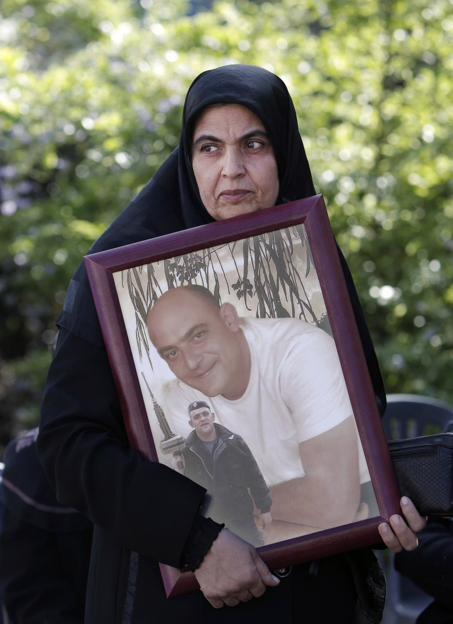 Inaam Omar, 50, aunt of one Lebanese soldier Ziad Omar who was kidnapped by Islamic militants, holds his picture during a demonstration to demand action to secure the captives' release, in front of government heaquarters in downtown Beirut, Lebanon, Monday, Nov. 17, 2014. The militants, including the al-Qaida linked Nusra Front and the extremist Islamic State group, are holding some 20 Lebanese soldiers and policemen hostages since August, when they briefly overran a Lebanese border town. (Bilal Hussein/Associated Press)