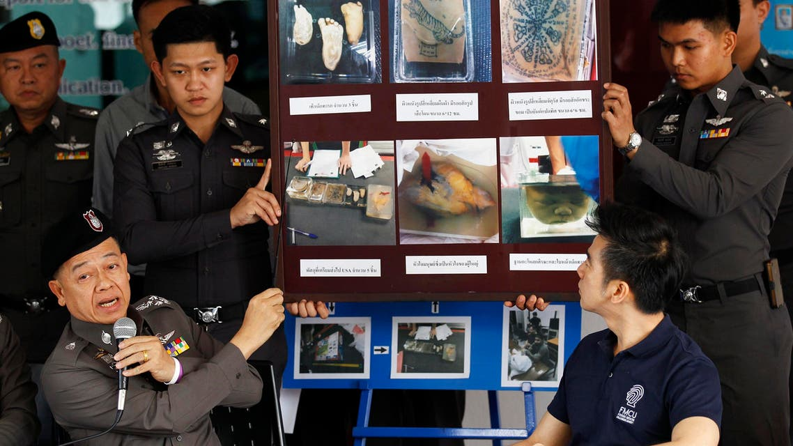 Policemen show pictures of body parts found in parcels as they address reporters in Bangkok November 17, 2014. (Reuters)
