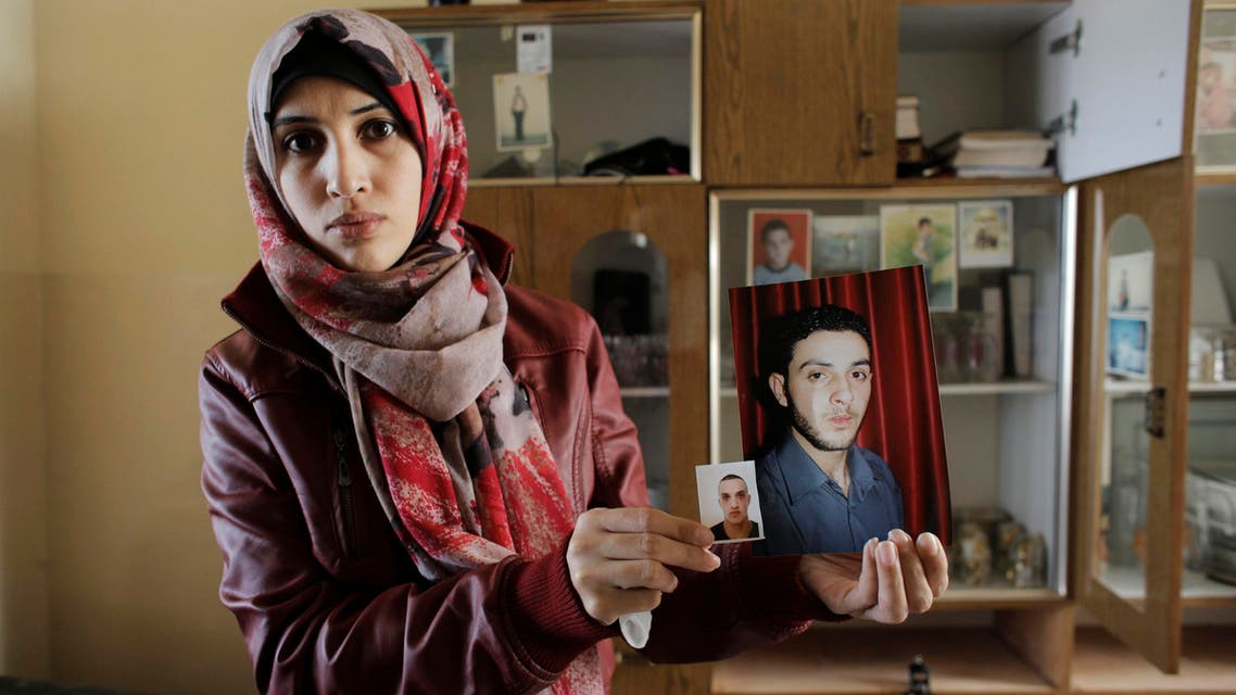 A relative of Ghassan and Udai Abu Jamal, cousins who killed four worshippers in a Jerusalem synagogue, holds their pictures at her home in the Jerusalem district of Jabal Mukaber November 18, 2014. (Reuters)