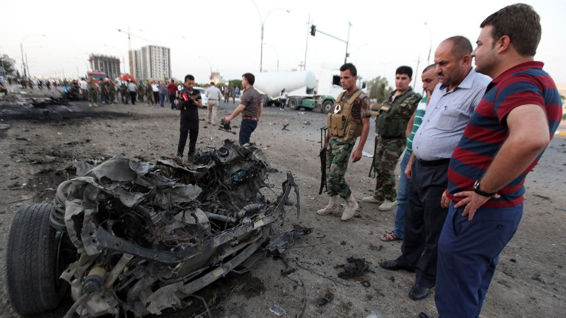 Kurdish security forces inspect the site of a car bomb attack in Arbil, the capital of Iraq's Kurdistan region, August 23, 2014.