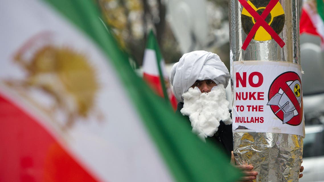 A demonstrator holds a mock-up of a nuclear missile with the lettering 'No nuke to the mullahs' as he protests against Iran's nuclear program and regime in front the Palais Coburg in Vienna on November 22, 2014. (AFP)