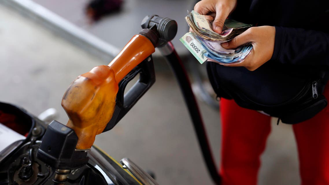 A worker at a state-owned Pertamina petrol station holds money as a motorcycle is filled with subsidised fuel in Jakarta October 31, 2014. Indonesia's new government will make changes to its costly gasoline and diesel subsidies before the end of the year, the country's chief economics minister said on Thursday. An advisor to President Joko Widodo, who was sworn in on Oct. 20, told Reuters earlier this month that a fuel price hike of 3,000 rupiah was planned by the new government, possibly as early as Nov. 1. REUTERS/Darren Whiteside (INDONESIA - Tags: POLITICS ENERGY BUSINESS)