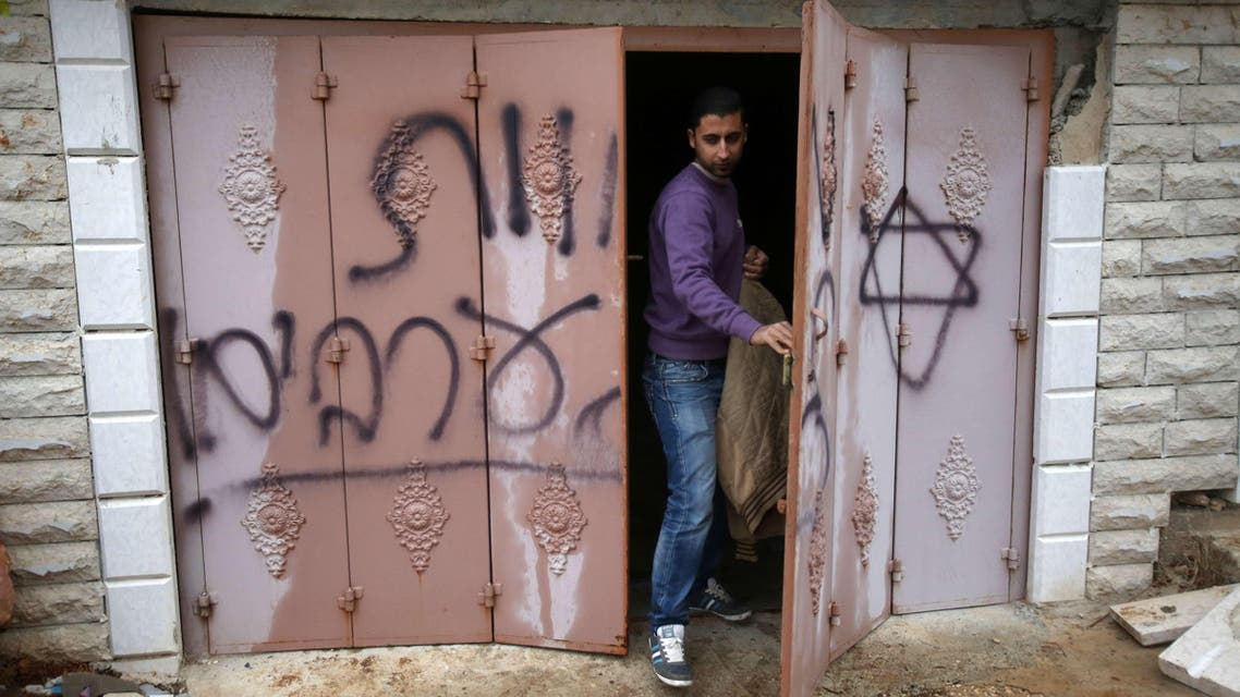 """A Palestinian man inspects a door at the Hamayel family that bears Hebrew writing which reads """"Death to Arabs"""", after an attack by suspected Jewish extremists, in a village northeast of Ramallah, on November 23, 2014. (AFP)"""