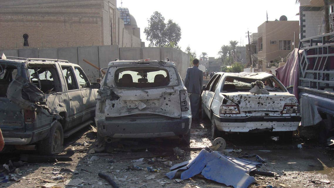 A man walks between destroyed cars at the site of a car bomb attack in Baghdad's Al-Mashtal district November 17, 2014. (Reuters)