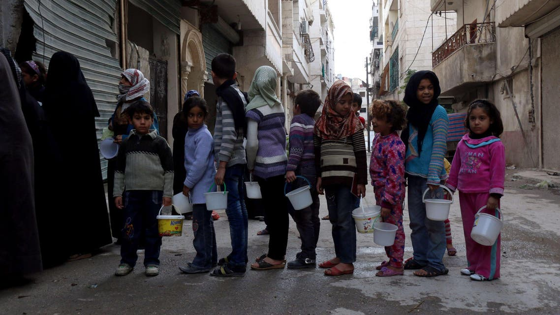 -, SYRIA : Syrian children queue up to receive food aid from a community kitchen that caters for impoverished families in the neighbourhood in the Myassar district of the northern city of Aleppo on November 23, 2014. In recent months, government forces have advanced around the outskirts of the eastern portion of the city that is under rebel control, threatening to encircle it completely. AFP PHOTO / ZEIN AL-RIFAI