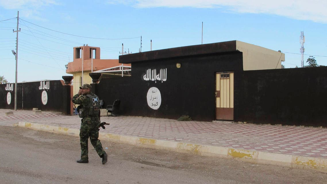 An Iraqi Shi'ite fighter walks past walls painted with the Islamist State flag, after Shiite fighters and Iraqi security forces took control of Saadiya in Diyala province from ISIS, November 24, 2014. (Reuters)