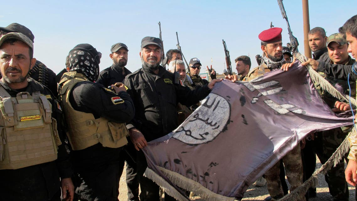 Iraqi Shiite fighters hold an Islamist State flag, which they pulled down from the frontlines after taking control of Saadiya in Diyala province from Islamist State militants, November 24, 2014. (Reuters)
