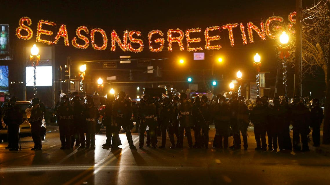Police form a line in the street under a holiday sign after a grand jury returned no indictment in the shooting of Michael Brown in Ferguson, Missouri November 24, 2014. (Reuters)