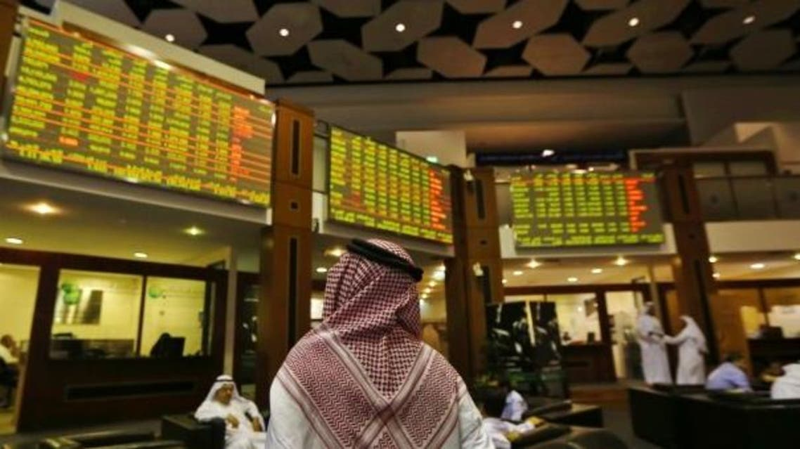 An investor looks up at screens displaying stock information at the Dubai Financial Market. (Reuters)