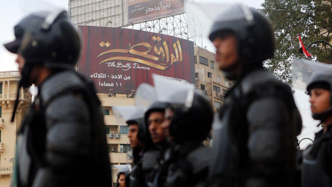 "Riot police take their positions in front of a billboard for ""The Belly Dancer"" television program on the third anniversary of the Mohamed Mahmoud street violence and deadly clashes at Tahrir Square in Cairo Nov. 19, 2014. (Reuters)"