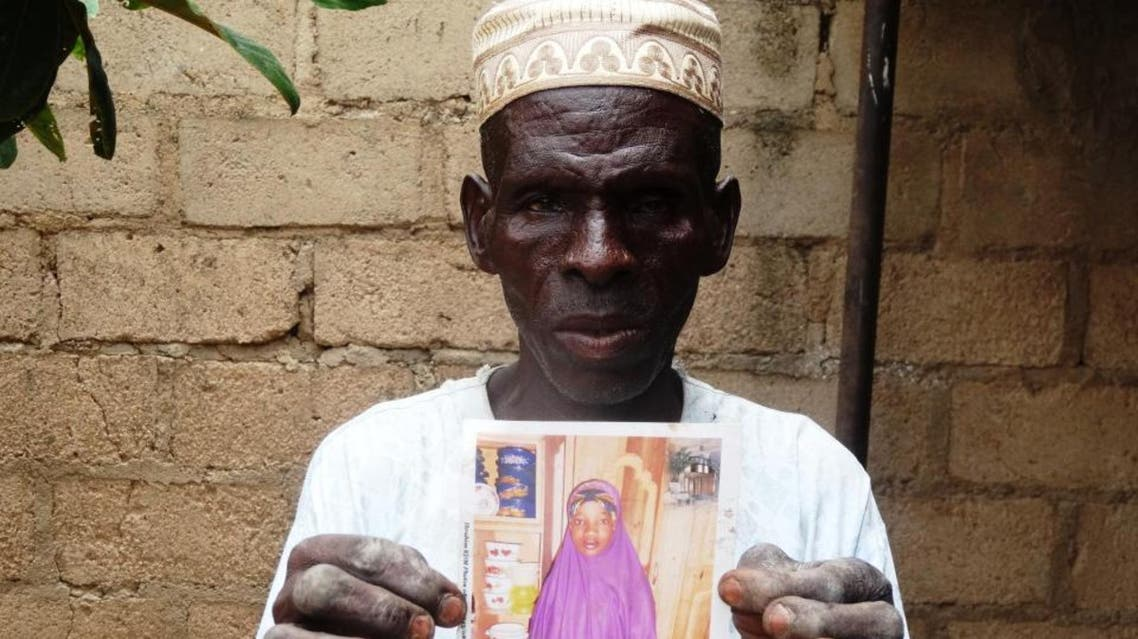 Sani Garba, 55, holds the picture of his 14-year-old daughter-in-law Wasila Tasi'u on August 10, 2014 inside her abandoned matrimonial home in the village of Unugwar Yansoro. (File Photo: AFP)