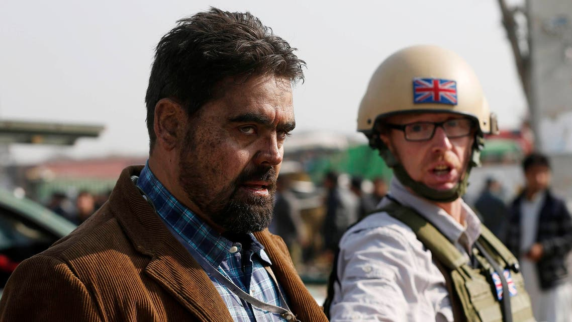 A British security official (R) escorts a survivor from the wreckage of a British embassy vehicle after a suicide attack in Kabul, Nov. 27, 2014. (Reuters)