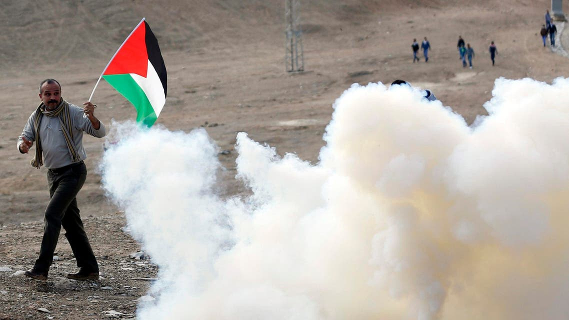 A Palestinian protester holds a Palestinian flag as he walks next to tear gas fired by Israeli soldiers during clashes following a protest near the West Bank city of Jericho November 28, 2014. (Reuters)