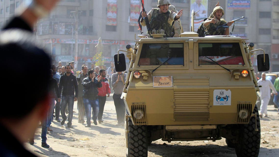 Army soldiers take their positions with their armoured personnel vehicles during clashes with supporters of Muslim Brotherhood and ousted Egyptian President Mohamed Mursi in the Cairo suburb of Matariya Nov. 28, 2014. (Reuters)
