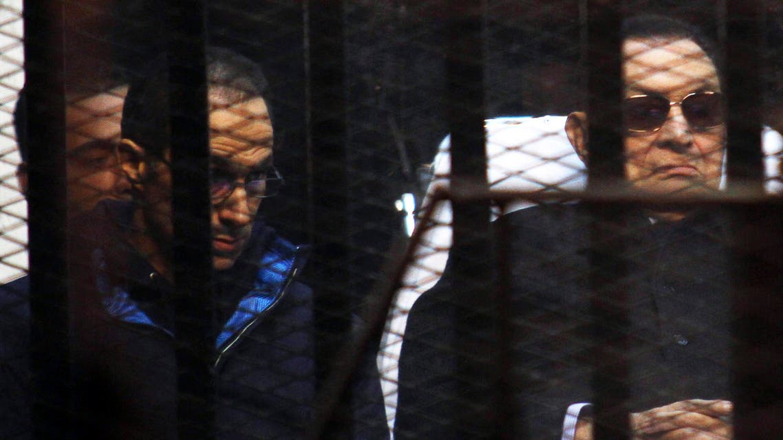 Former Egyptian President Hosni Mubarak listens next to his son Gamal (L) inside a dock during his trial at the police academy on the outskirts of Cairo November 29, 2014. (Reuters)