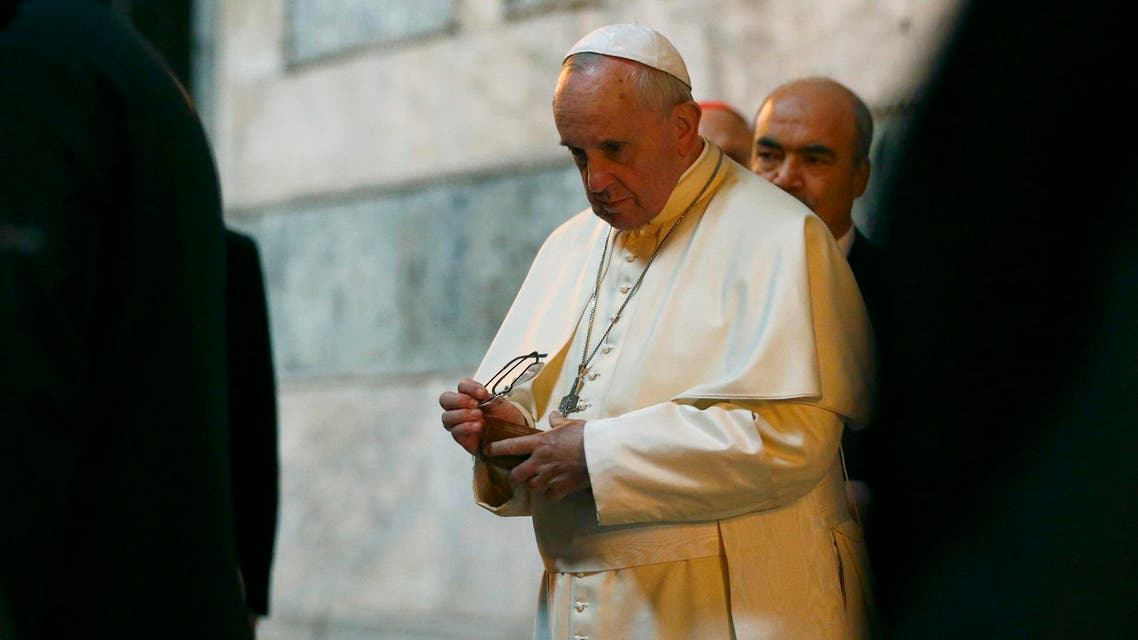 Pope Francis puts away his reading glasses after signing the guest book inside the Saint Sophia Musem during his visit to Istanbul November 29, 2014. (Reuters)
