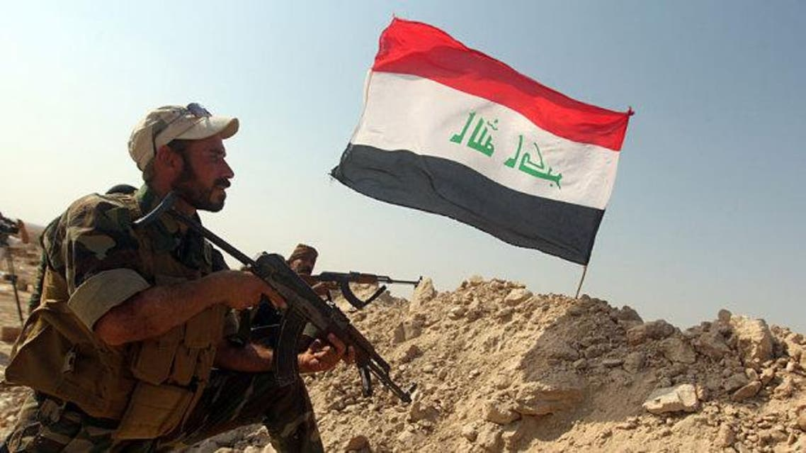An Iraqi fighter guards a front line position flying the Iraqi flag in the Anjana area ten kilometres south of the town of Amerli. (AFP)