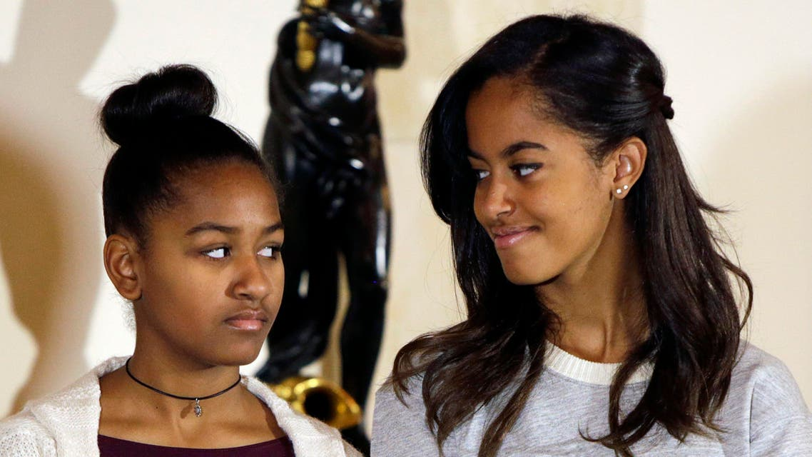 """U.S. President Barack Obama's daughters Sasha (L) and Malia listen to their father during the pardoning of the National Thanksgiving Turkey """"Cheese"""" at the White House in Washington November 26, 2014. (Reuters)"""