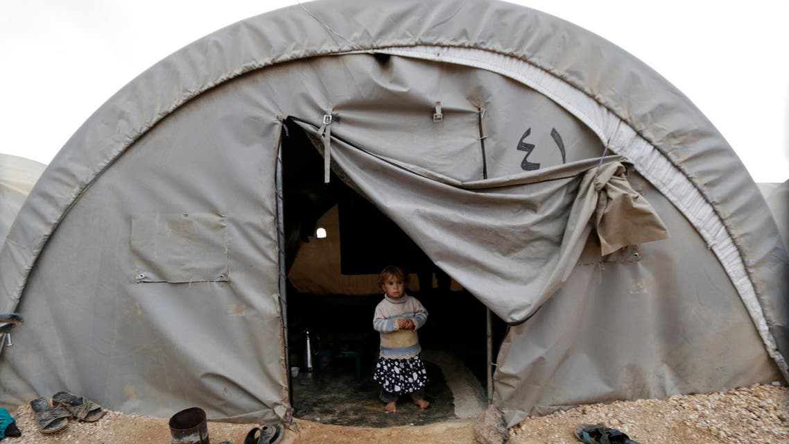 A child, who is internally displaced due to fighting between rebels and forces loyal to Syrian President Bashar al-Assad, peeks out from a tent at the Jarjanaz refugee camp in Idlib November 30, 2014. (Reuters)
