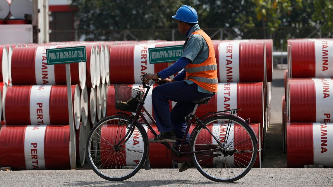 An employee rides his bike past barrels of petroleum products at a state-owned Pertamina fuel depot in Jakarta September 9, 2014. (Reuters)