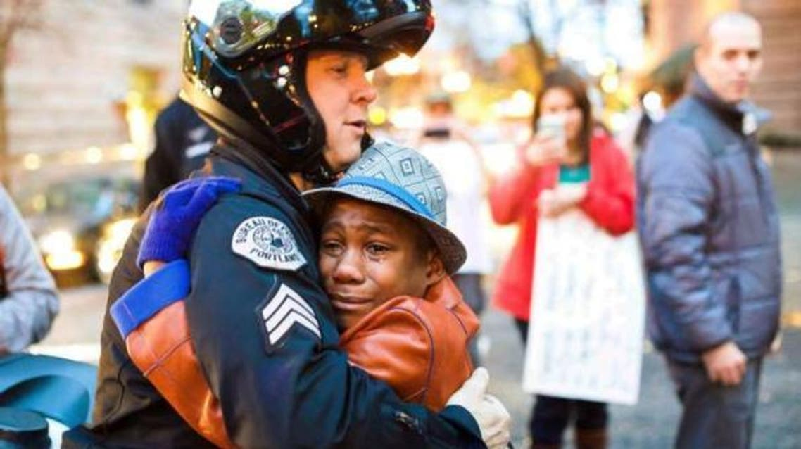 Portland police Sgt. Bret Barnum, left, and Devonte Hart, 12, hug at a rally in Portland, Ore., where people had gathered in support of the protesters in Ferguson, Mo. (Photo courtesy: AP/Johnny Nguyen)