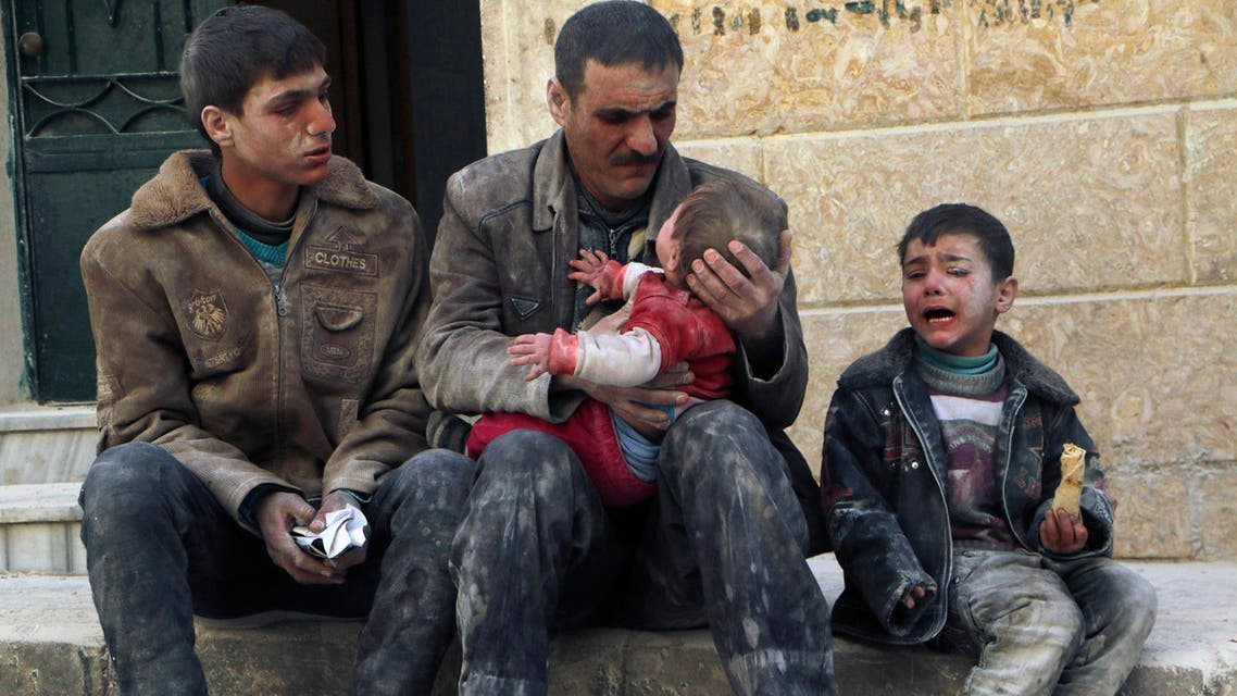 A man holds a baby saved from under rubble, who survived what activists say was an air strike by forces loyal to Syrian President Bashar al-Assad, in Masaken Hanano in Aleppo, in this February 14, 2014