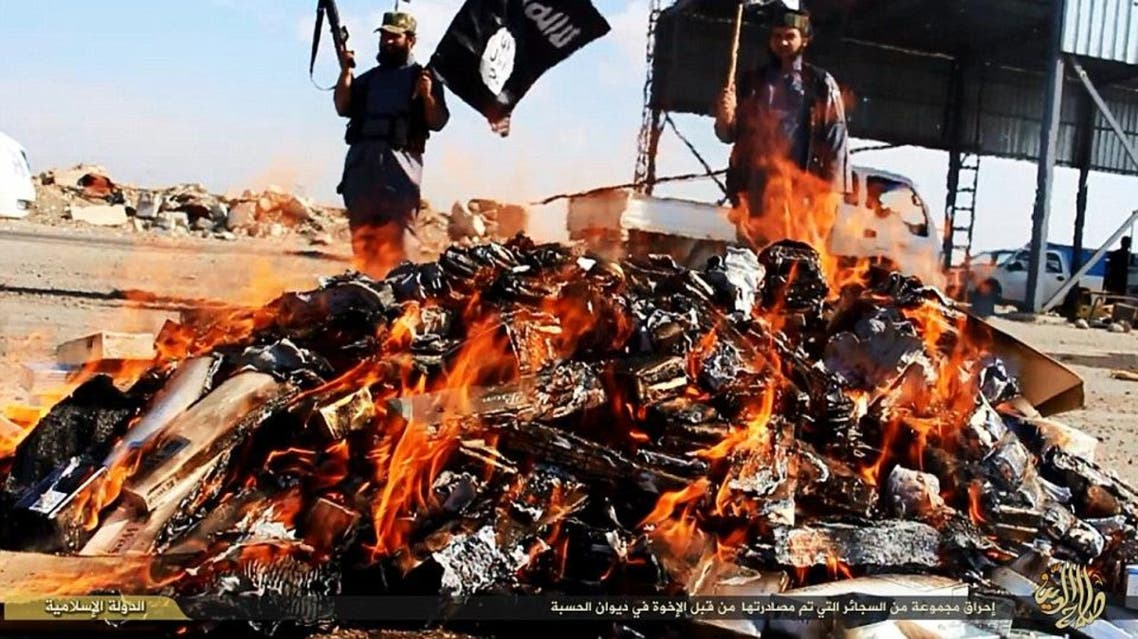 A pile of cigarettes, banned in ISIS-held areas, burn as the militants watch over. (Photo courtesy: YouTube)